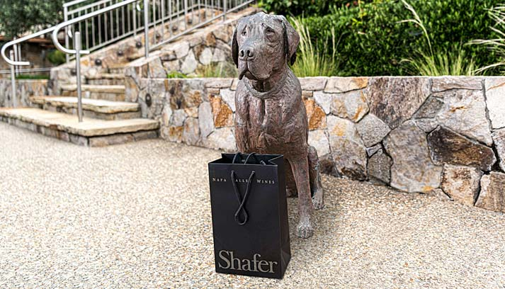 Sculture of Tucker the dog with bag of Shafer goodies.